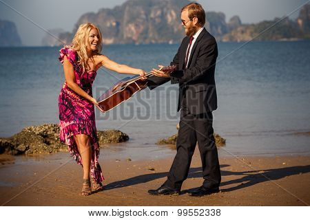 Blonde Takes Guitar From Guitarist On Beach