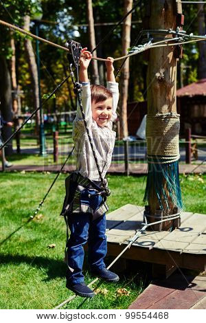 excited little boy having fun in rope park