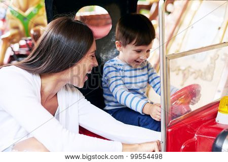 happy woman with little boy having fun on merry-go-round