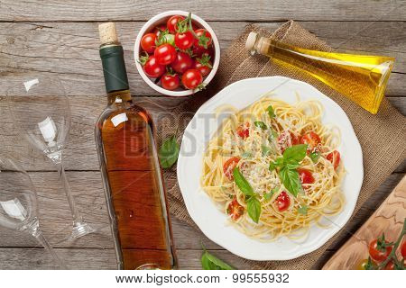 Spaghetti pasta and and white wine on wooden table. Top view