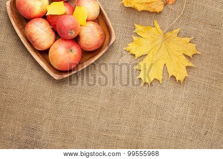 Autumn leaves and apples over burlap texture background with copy space
