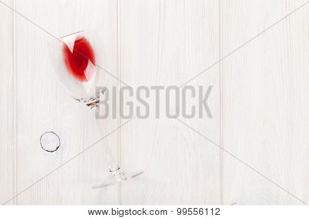 Red wine glass over white wooden table with copy space