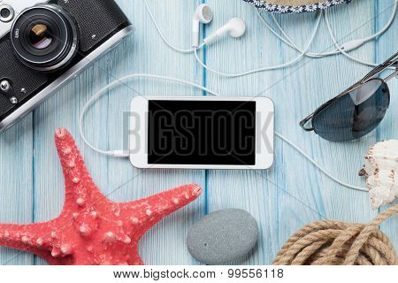 Smartphone and camera on wooden table with starfish and shells. Top view with copy space