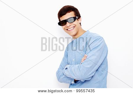 Young hispanic man wearing jeans shirt and 3D TV LCD shutter glasses standing with crossed arms and smiling against white wall - 3D film concept