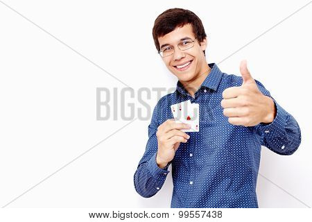 Young hispanic man wearing blue shirt and glasses holding two aces (hearts and diamonds) in his hand and showing thumb up hand gesture with smile against white wall - gambling concept