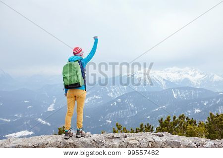Back view of young woman wearing pink hat, blue jacket, green backpack, yellow pants and hiking boots raising her hand against winter mountains celebrating successful climb - goal concept