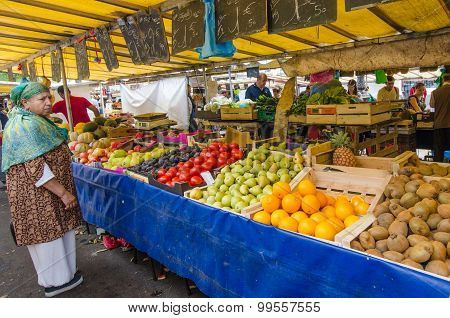 Woman shops for fresh produce at the Bastille market in Paris