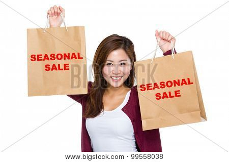 Asian woman raise up the shopping bag for showing seasonal sale