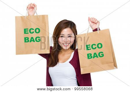Asian woman raise up the shopping bag for showing eco bag