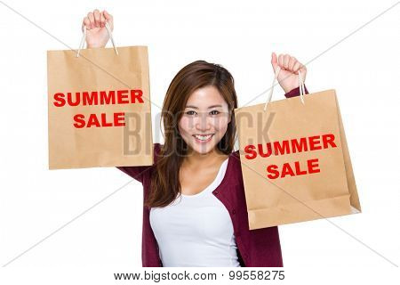 Asian woman raise up the shopping bag for showing summer sale