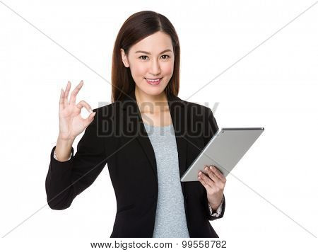 Asian young businesswoman use of the tablet pc with ok sign gesture