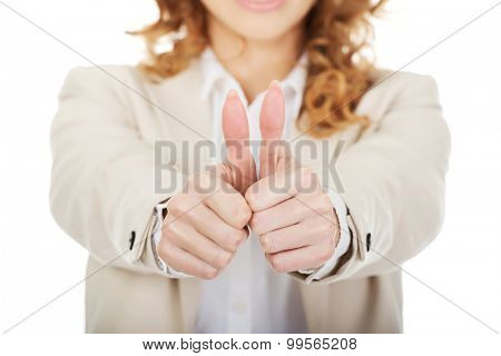 Happy businesswoman with thumbs up gesture.