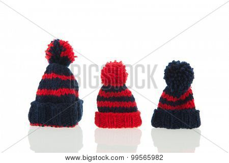 Red and blue knitted winter hats isolated over white background
