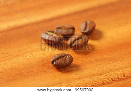 Five roasted coffee beans on wooden table
