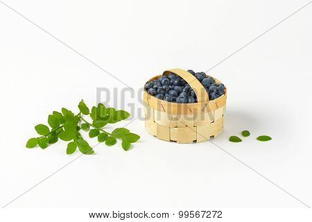 wooden basket with fresh blueberries and green leaves