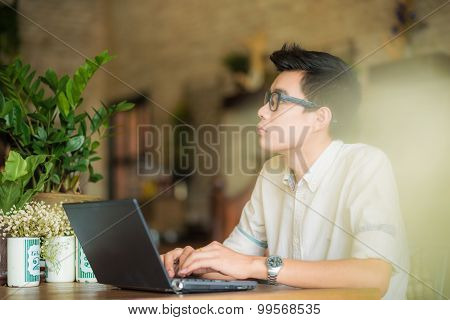 Young Asian Man Drinking Coffee In Cafe And Using Laptop Computer