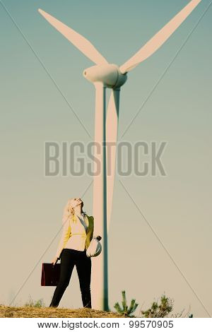Model posing in front of wind power generator