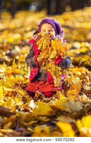 Little girl playing with autumn leaves in the park