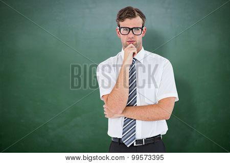 Serious geeky businessman thinking and holding his chin against green chalkboard
