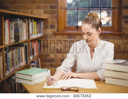Blonde teacher correcting in the library in school