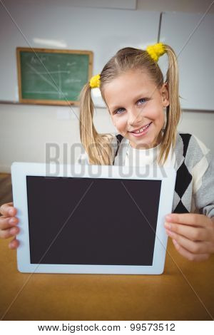 Portrait of smiling pupil showing tablet to camera in a classroom
