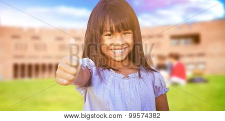 Cute little girl against students using laptop in lawn against college building