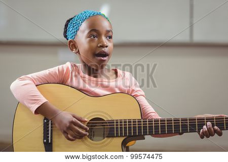 Cute pupil singing and playing guitar in a classroom in school