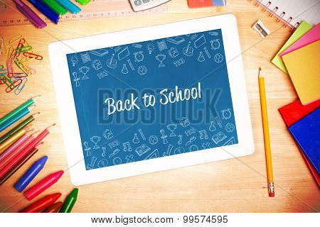 The word back to school and school wallpaper against students desk with tablet pc