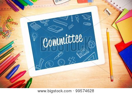 The word committee and school doodles against students desk with tablet pc
