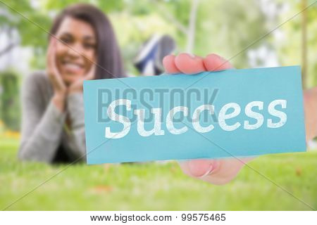 The word success and hand showing card against pretty brunette smiling at camera in park