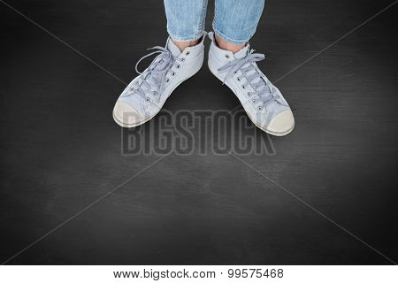 Woman wearing trainers against black background