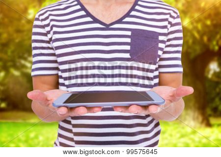 Close up of man holding tablet against trees and meadow in the park