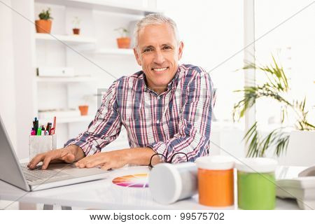 Portrait of smiling casual designer working with laptop in the office