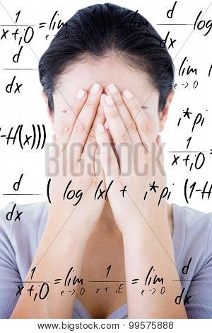 Sad woman hiding her face against maths equation