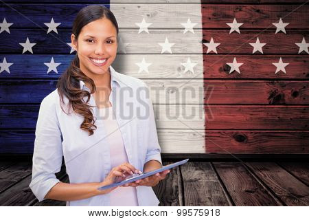 Woman using tablet pc against composite image of usa national flag