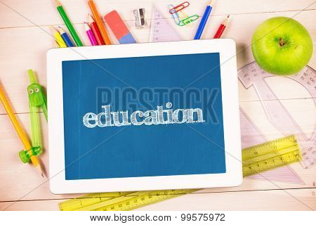 The word education and students desk with tablet pc against blackboard with copy space on wooden board