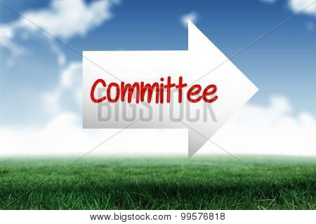 The word committee and arrow against blue sky over green field