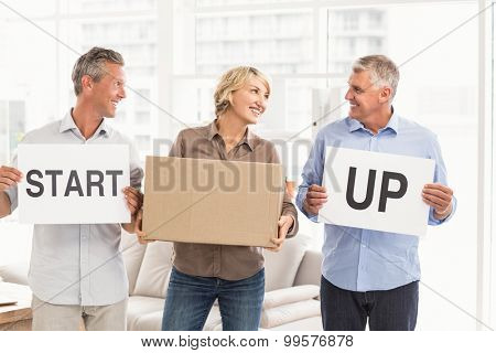 Smiling casual business people holding start up sign in the office