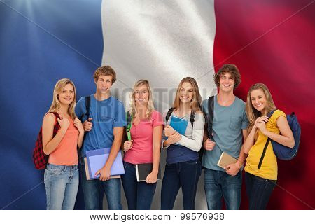 Smiling students wearing backpacks and holding books in their hands against digitally generated france national flag