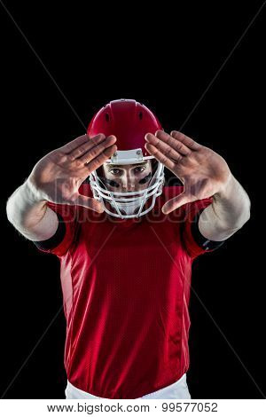 Portrait of american football player protecting himself against black background