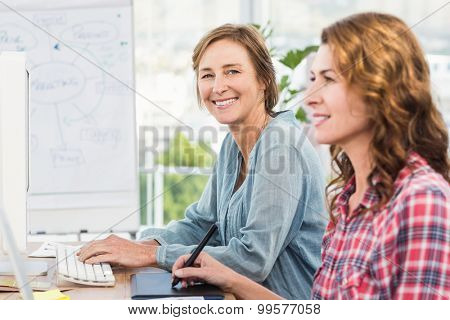 Casual businesswomen looking at computer in an office