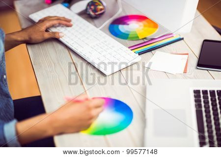 Graphic designer working with colour chart at workplace