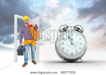 Handyman holding tool box and multimeter against alarm clock counting down to twelve