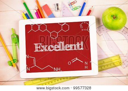 The word excellent! and science graphic against students desk with tablet pc