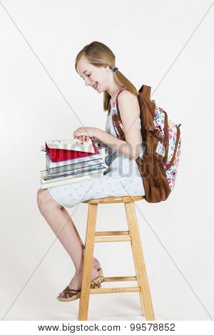 Portrait of friendly school girl student with backpack, sitting on a stool, holding notebooks and reading