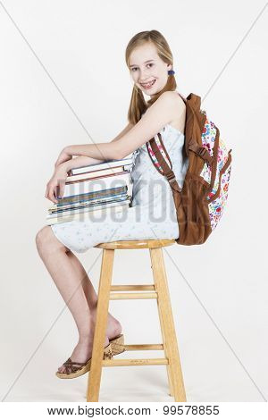 Portrait of friendly school girl student with backpack, sitting on a stool, holding notebooks and composition book