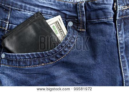 Wallet with dollars in the pocket of jeans