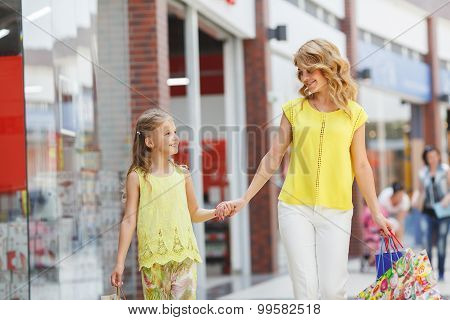 Mother and the daughter with bags in a city supermarket