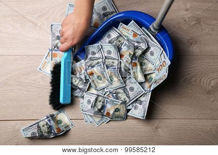 Woman broom sweeps dollars in garbage scoop on wooden floor background