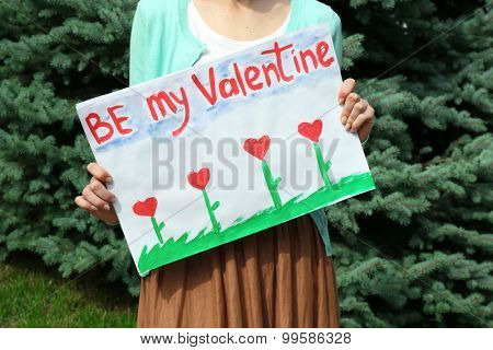 Woman holding poster with phrase BE MY VALENTINE, outdoors